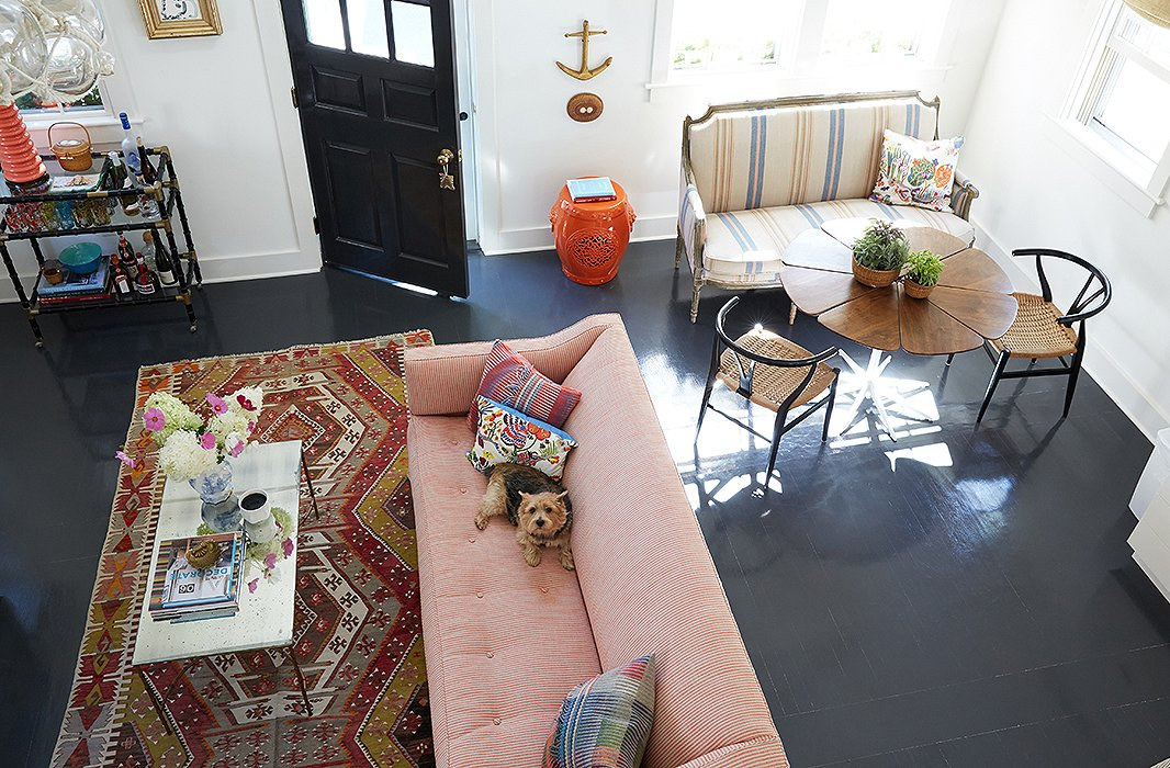 "The dark floors contrast perfectly with Elizabeth's more upbeat choices (""I do love color, and I do love pattern,"" she admits). Overall the decorator took her design cues from the seaside location, making sure to nail that ""old Nantucket spirit"" without being overly reverential. ""These are the original floors,"" she notes. ""We were going to rip them out but instead decided to sand them down and paint them a historical gray."" Find a similar garden stool here."