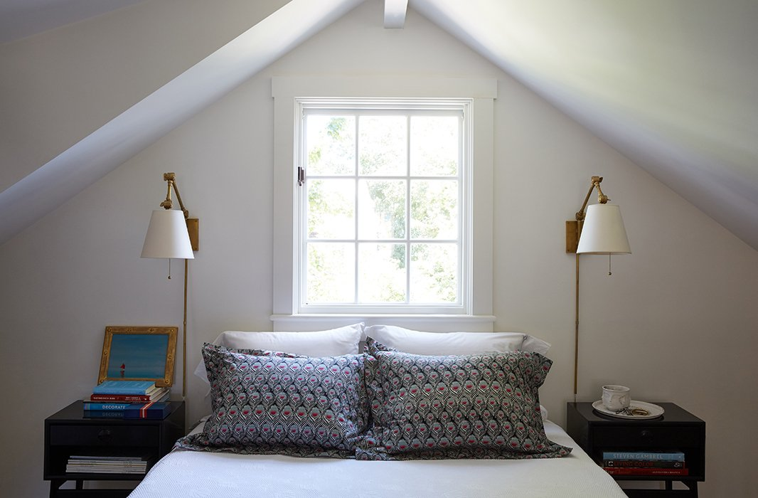 """The most minimalist space in the home is the master bedroom. Because of the angular ceiling lines (""""The architecture is the architecture""""), Elizabethchose not to dress the window, and the room couldn't accommodate a headboard. """"Besides, we're up and out here and off to the beach, so I just kept it simple,"""" she says. Shefell head over heels for the muted Liberty of London peacock-feather bedding, however. """"It's actually an odd choice for me, because I don't do a lot of dark colors.But with the gray floor and white walls, it works."""""""