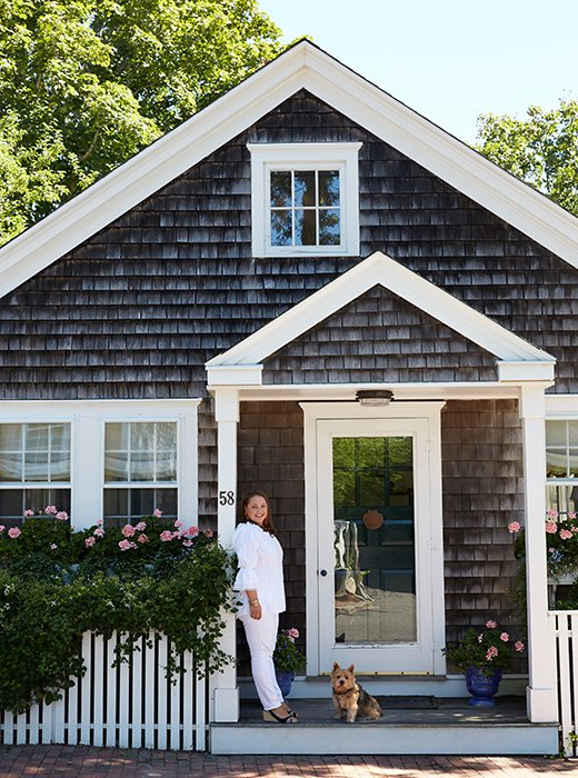 Elizabethand the family's Norwich terrier, Lily Bear, strike a welcoming pose at the cottage, which was once a turn-of-the-century butcher shop.<br />