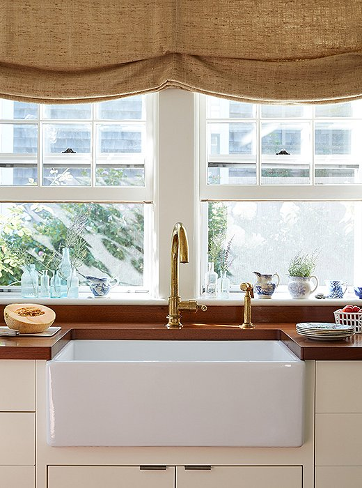 "In keeping with the home's loosely nautical theme, Elizabeth chose to use all brass fixtures: plumbing, lighting, hardware—everything. Not that she's cooking up five-course dinners in the kitchen. ""It's small, so we do easy suppers and cocktails and breakfasts. We're out a lot, honestly. We're on our boat all the time."""