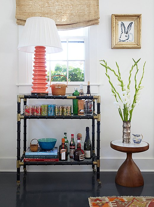 """It's a real mix of high-low,"" says Elizabeth of the space, pointing out the bar cart from Paris, a Hunt Slonem framed bunny print, and the sinuous midcentury-style table. But the most meaningful piece here is undoubtedly a Nantucket ""lightship basket"" passed down from her grandmother. Baskets like this one were originally made by the crewmen of lightships as a way to pass time while away at sea."