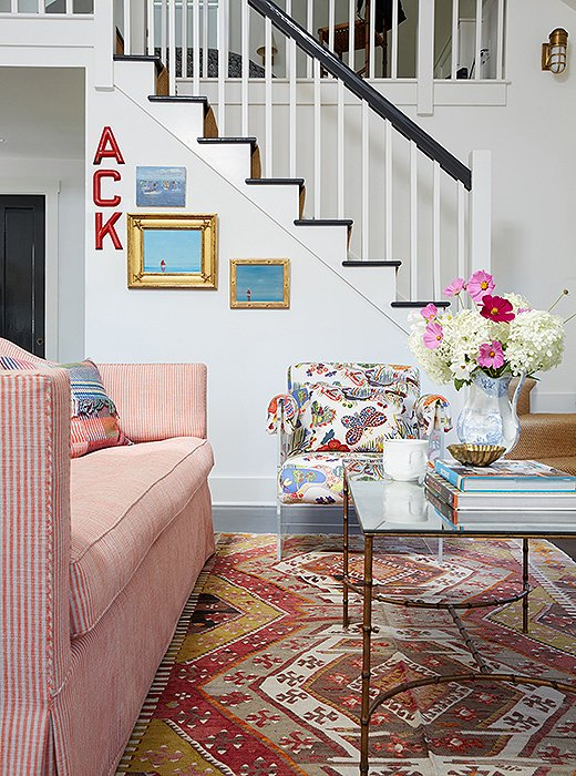 "Elizabeth's pro touch is evidenced in her ability to make a Josef Frank butterfly-print chair coexist peacefully with an equally lively kilim rug and a striped sofa. That this is a vacation home allowed her to really up the color and pattern ante plus let her more eclectic side play out. Cue the letters spelling out ""Ack,"" which is actually a nickname for Nantucket, not an expression of annoyance."