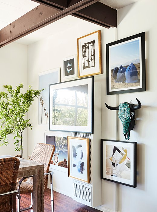 Mid-century Modern design style expressed with an eclectic art gallery wall in the dining room of a cottage guest house by Sophia Bush. #gallerywall #midcentury #modern #walldecor