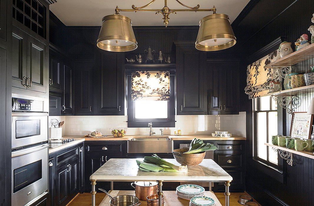 "The kitchen had been renovated by the previous owner but wasn't Bailey's style. Since the room doesn't get much light, the designer embraced the darkness by painting the cabinets a glossy black. She added a fixture from Circa Lighting as a nod to the home's rich past. ""I just wanted something that felt kind of Victorian but then also had a modern vibe to it."""