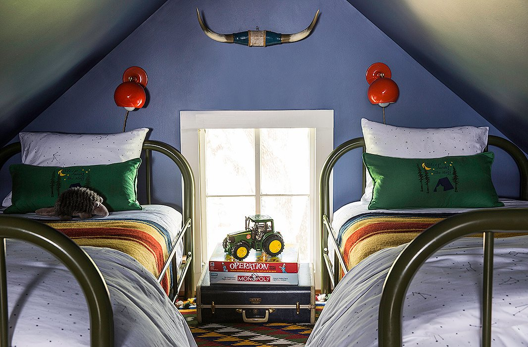 "Constellation-print bedding by Biscuit Home, Pendleton blankets, and army-green Schoolhouse Electric beds in the loft let little guests feel as if they're sleeping under the stars. ""We kept it a dark blue like the night sky and wanted it to feel a like an old-timey boys' camp,"" Bailey says."