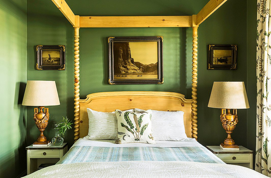 "Like the kitchen, this guest room receives minimal light, so Bailey went with Benjamin Moore's Alligator Alley for the wall color. ""We wanted to make it feel like a cozy cocoon,"" she says. The deep green provides a beautiful contrast to the natural-wood four-poster bed and the ornate table lamps."