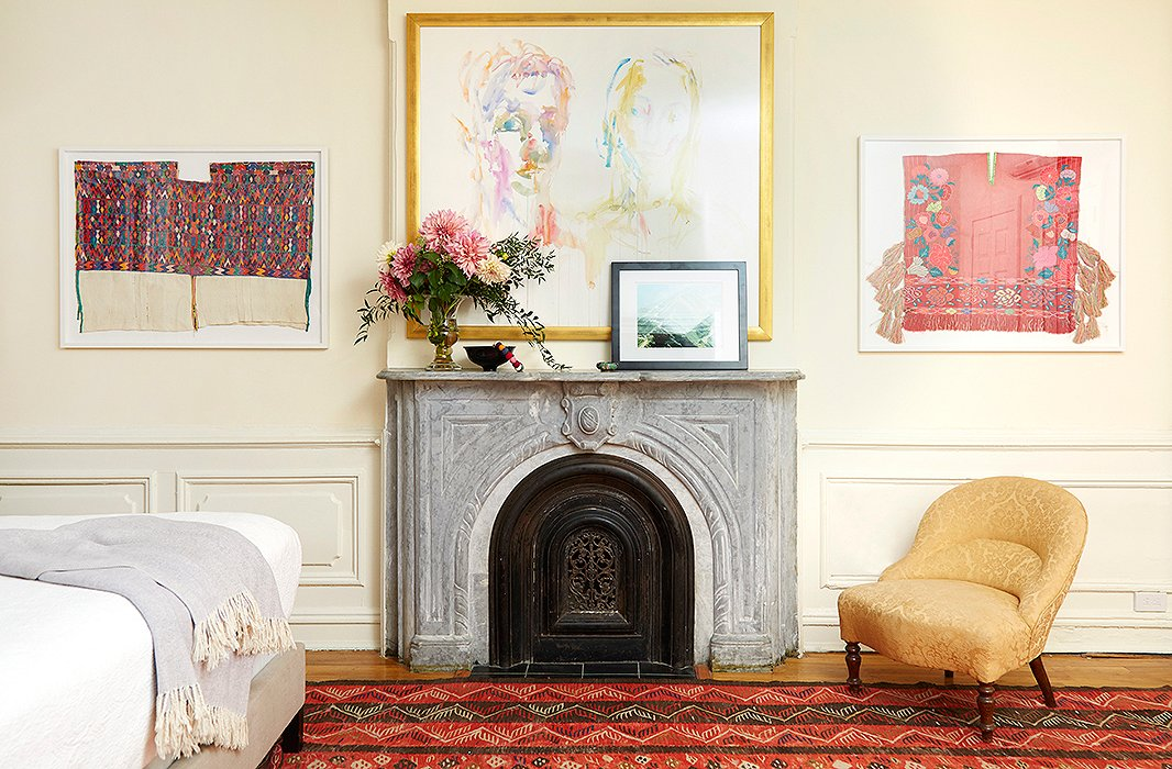 Carefully floating in Framebridge frames, two Mexican textiles became elegant wall hangings to complement a watercolor portrait. A photograph of a Haitian mountain leans against the mantel.