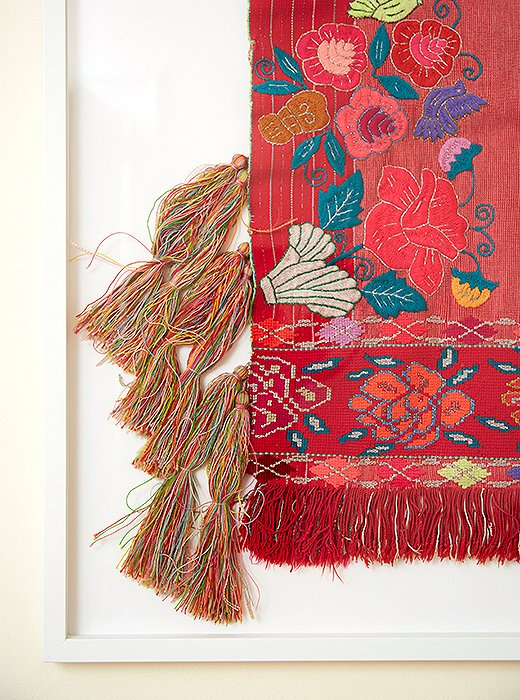 A Mexican textile floating (actually, sewn) on a mat to highlight its textured tassels and embroidery. Frame by Framebridge.