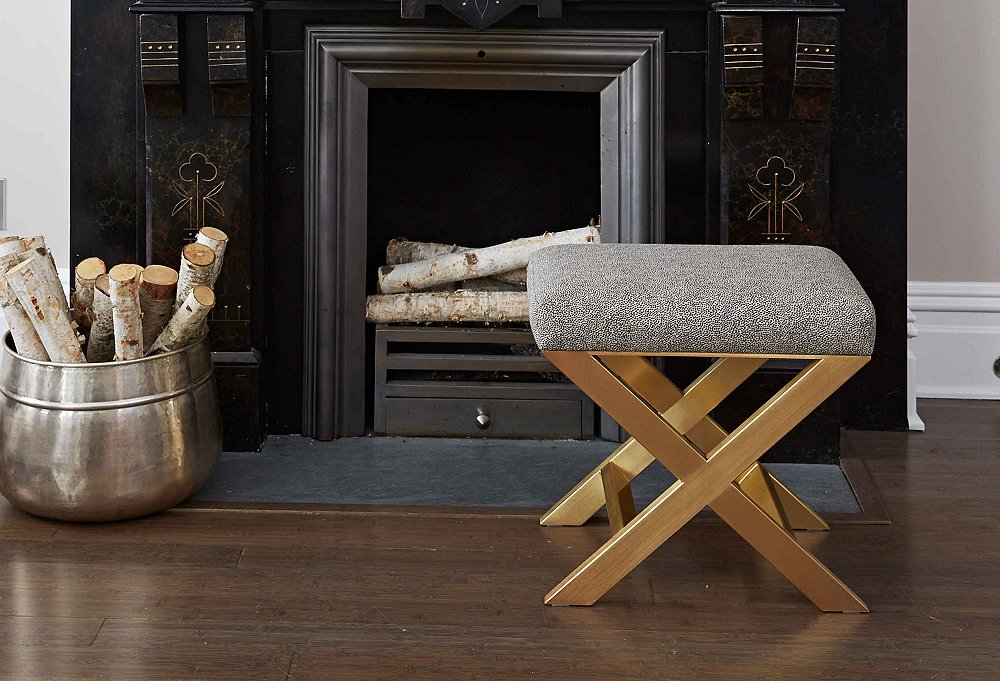 We love how the glimmering brass base on this glam ottoman wonderfully complements the beautiful carvings on the stone fireplace.
