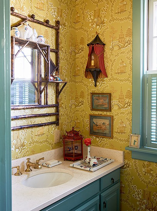 "The designers used a vintage chinoiserie wallpaper to add impact to a small powder room and displayed objects and art on the walls and the vanity. ""Bathrooms can have collections too,"" notes Jason."