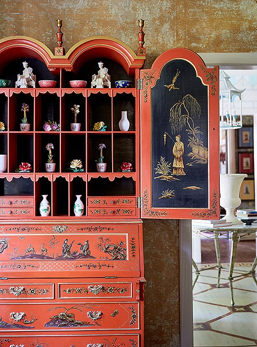 "Jason and John filled the ""dragon-lady red"" lacquered secretary with a collection of porcelain flowers. ""That piece is a little more decorative, but we also use it as a writing desk,"" says Jason."