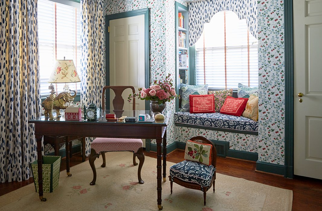 The designers scored a vintage strawberry wallpaper from Brunschwig & Fils and used a mix of Madcap Cottage fabrics and needlepoint pillows from the estate of C.Z. Guest to create a cozy reading nook.