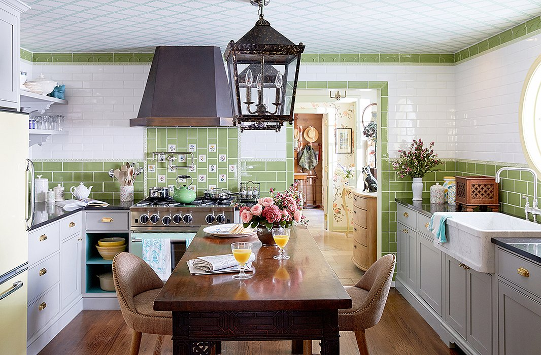 "John and Jason gave the kitchen a total makeover inspired by the Royal Pavilion in Brighton, England. ""We pretty much wanted to do an English country-house kitchen with tile from floor to ceiling,"" Jason explains. They found floral tiles in Portugal and integrated them into the green-and-white scheme. They added vintage lanterns above the island, which is actually an 18th-century table that they had raised."