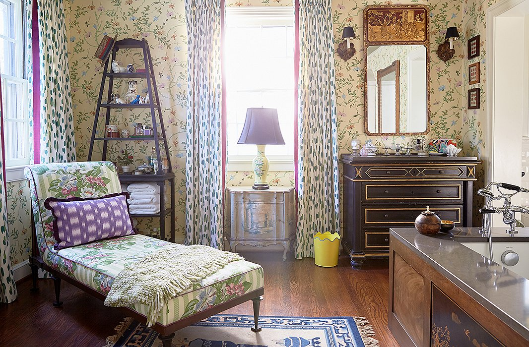"Antiques are used prominently throughout the house, even in the master bath. A vintage chinoiserie panel was set into the side of the tub, and they converted an 18th-century chest into a sink vanity. ""You want to sit in the tub for hours and read World of Interiors and drink a martini,"" Jason says. ""It's so warm and inviting."""