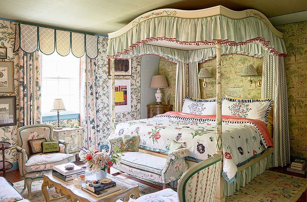"John and Jason used an ""explosion of print and pattern"" in the master bedroom. ""It feels very much of the house in its heyday but contemporized,"" says Jason. A decorative painter added chinoiserie details to the canopy bed's original floral motifs. ""You can take something that you buy and reinvent it and add a further spin of your own,"" John says."