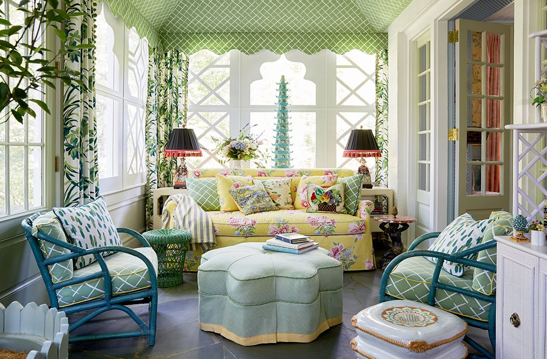 "The sunroom is tented in Madcap Cottage's Cove End fabric. ""Who doesn't love a tented room?"" asks Jason. ""It makes you feel like you're a kid in your backyard minus that sprinkler that turned on at 2 o'clock in the morning."" They added a cheerful yellow sofa and casual rattan chairs. ""The idea was to create a space that was fun and relaxed and made you happy,"" he adds."