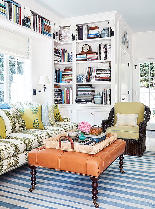 "The cozy family room is a study in pattern and texture. ""I love the mix of upholstery fabrics with the leather ottoman and wicker chairs,"" says Mark. ""The bookshelves balance the kitchen cabinets across the room."" The rug is antique, and the tray is Ralph Lauren Home."