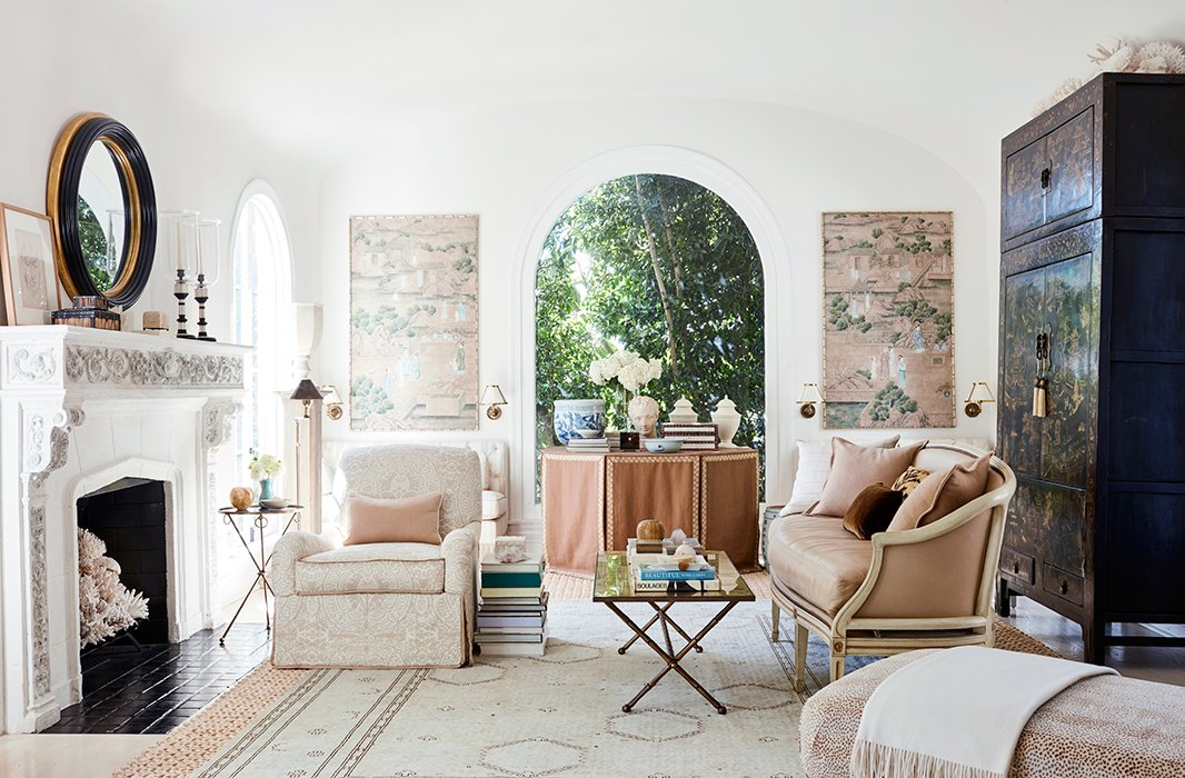 """The wallpaper panels that flank the arched window inspired the overall design of the serene living room. """"I love the pattern of these Gracie wallpaper panels.They really set the palette for the room,"""" Mark says.""""The last time I redecorated I pulled the window treatments down because I really wanted the architecture of the room to open, and the arch windows are so beautiful."""" An 18th-century chinoiserie armoire presides over the multiple seating areas."""