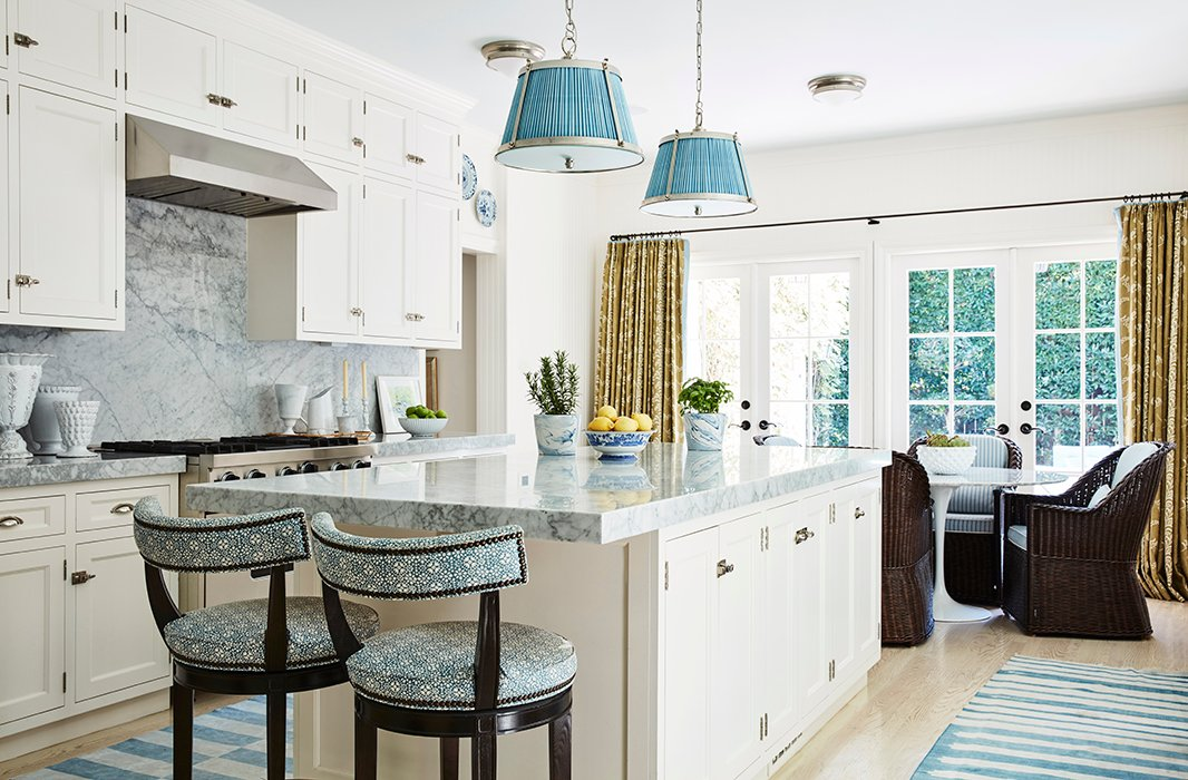 "The designer combined the original galley kitchen and adjoining maid's room to achieve an open, airy blue-and-white space that is another multifunctional area. ""We don't cook a lot, so it really serves as a family room,"" says Mark. ""The TV is here, and we have lots of seating areas."""