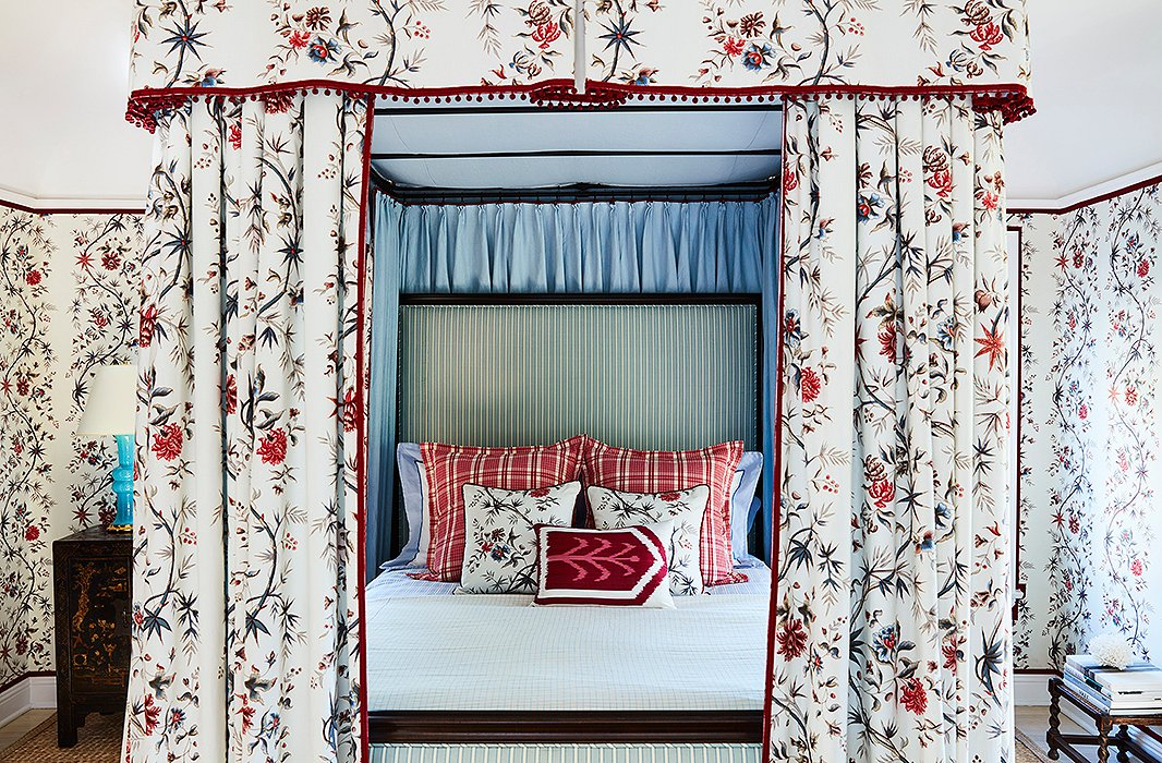 A blue-green stripe serves as a grounding pattern for a bed covered in chintz, plaid, and ikat. Photo by Joe Schmelzer.