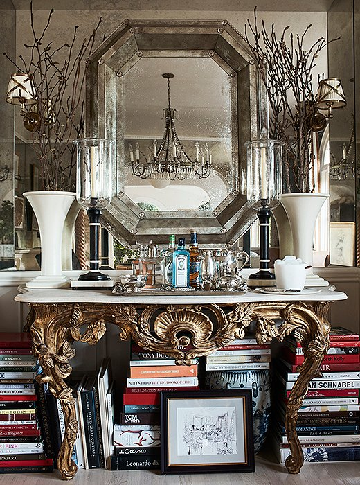 "A gilded console at one end of the dining room houses a bar and more of Mark's design books. ""We don't formally entertain,"" he says. ""So I wanted this to be a place where I could sit and work too."" The hurricane lamps are from his friend John Rosselli's antiques shop. The custom mirror was made from antique glass."
