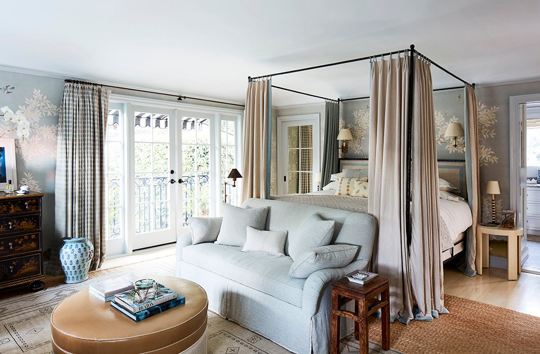 """Mark's favorite space, the master bedroom, is dressed in a Gracie paper. """"I call it China blue and use it in many bedrooms because it's so calming.This room is very functional. We made it bigger and added cabinetry.It's truly a room we live in."""" The settee and the ottoman are custom."""