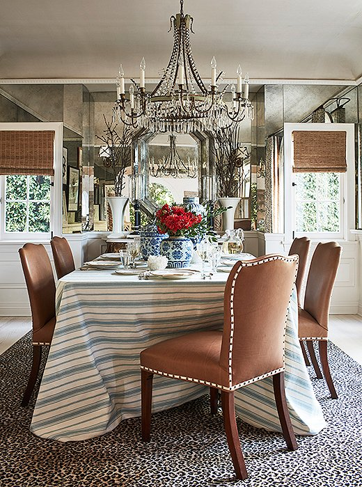 """The dining room had a racy wallpaper,"" says Mark. ""I took it out and mirrored the space so it would feel bigger and reflect the outdoors."" Adding extra character are leather-covered chairs, a cheetah-print rug, and an antique chandelier. ""Everything kind of glistens and shines in here."""