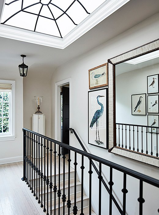 "The skylight on the upstairs landing brings in lots of California light. ""It adds drama and height to the space,"" says Mark. Custom wrought-iron railings echo the window's design. The bird prints are inspired by his friend Bunny Williams's home in the Dominican Republic—""one of my favorite homes anywhere."""