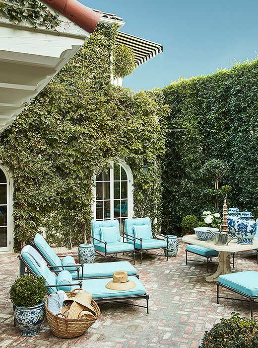 "A courtyard, framed by ficus hedges, makes a lush spot for relaxing or dining year-round. ""I love this antique stone table, even though it's crumbling, and designed the entire space around it,"" Mark says. ""We use it for dining, as a bar, or just as a focal point."" A straw tote is filled with sun hats; garden stools are used as both side tables and seating."