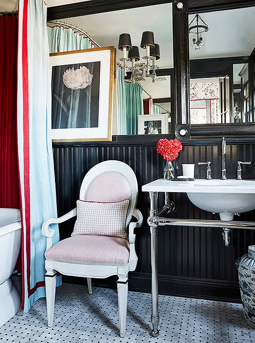 "The lacquered black bath off the guest room is balanced with a series of mirrors. ""It makes it all feel bigger, and the black works with the red bedroom,"" says Mark. The armchair is a Bunny Williams design."