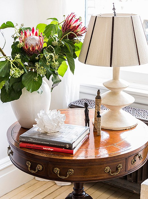 Throughout the home, unexpected pairings lend an eclectic, well-collected vibe. Case in point: an antique library table topped with a sculptural Giacometti-style lamp, alongside a crystal votive and African figurines picked up on husband Averill's travels.