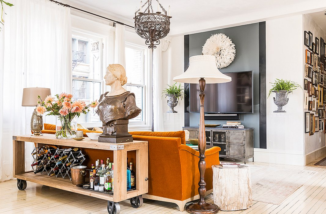 "A favorite of the kids, this ""supercasual"" seating nook is ideal for curling up to Netflix marathons and Sunday football games. To downplay the TV, Katie turned to one of her favorite decorating tricks: a glossy stripe of black paint. Plexiglas pedestals bookend the setup, and a bust of Joan of Arc (""the first antique I ever bought"") keeps watch over the dining area."