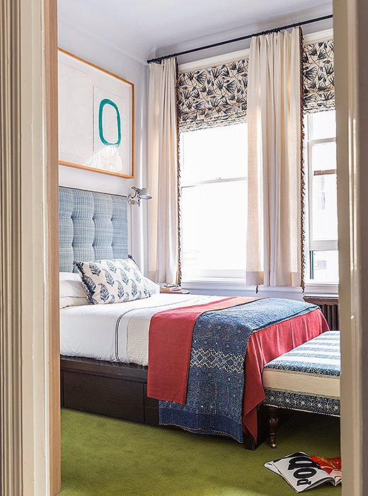 In the third bedroom, a printed ottoman and throw pillow from Katie's collection for One Kings Lane complement curtain fabric from her first textiles collection. The papyrus-leaf pattern takes cues from ancient Egyptian wall paintings.