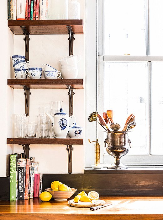 "Open shelving provides space for pieces in constant rotation. Katie describes her entertaining style as ""low-key but comfortable."" Whether she's serving a spread of ready-made cheese platters or a home-cooked risotto, the vibe is casual: Guests pitch in with prep, and parties spread throughout the space."