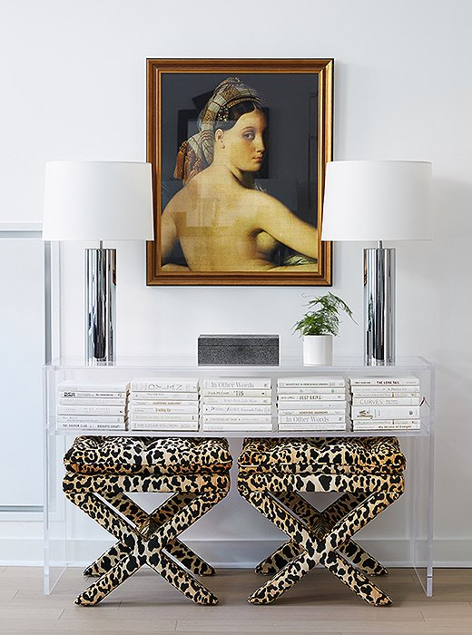 "David tucked leopard-print stools beneath an acrylic console. ""They bring in a sense of weight and texture and draw your eye to that vignette."" He added the vintage lamps to play off the chrome pieces in other parts of the room."