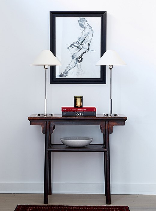 "David focused on adding light in another entry vignette. ""There's a flush mount on the 11-foot ceilings, but that was really the only light source. We brought in the two lamps and put them on a vintage Chinese altar table."""
