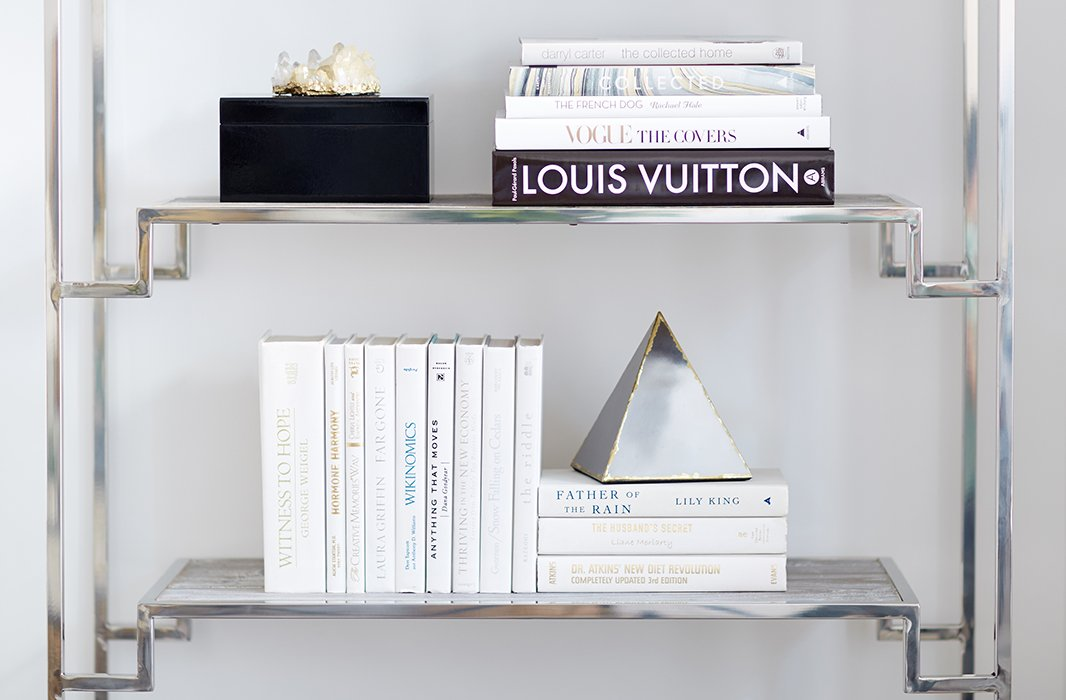 "White books and a few geometric accents keep the étagères from feeling cluttered. ""I think that there is an interesting tonal play between the books and the wall color,"" David says. ""Even though the books were published in the '50s, '60s, and '70s, they feel more modern and up-to-date because they're all color-blocked in one shade."""