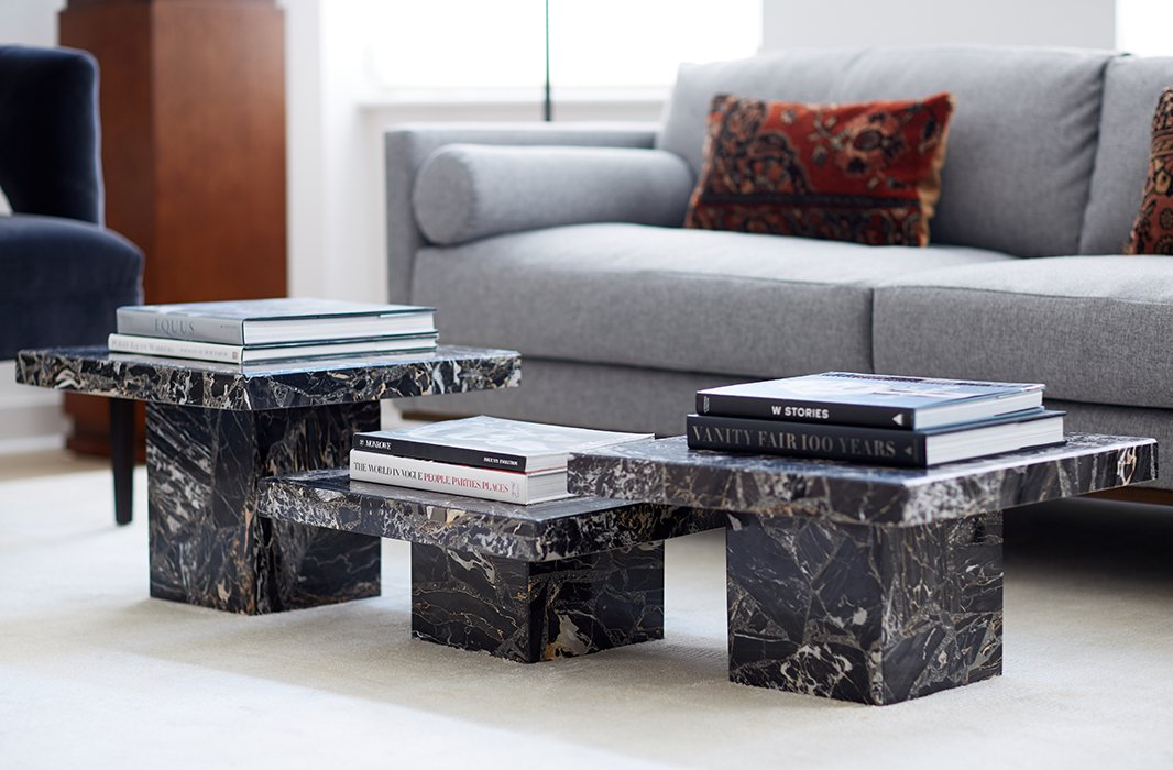 "The coffee table is actually three side tables clustered together. ""It anchors the room and provides a sculptural touch,"" David explains. ""I just wanted something really clean and simple. I think that those tables are almost like pedestals."""