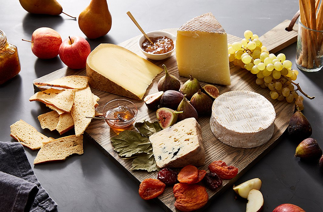 A wood board adds to the organic beauty of this delicious display of cheeses and seasonal fruits.