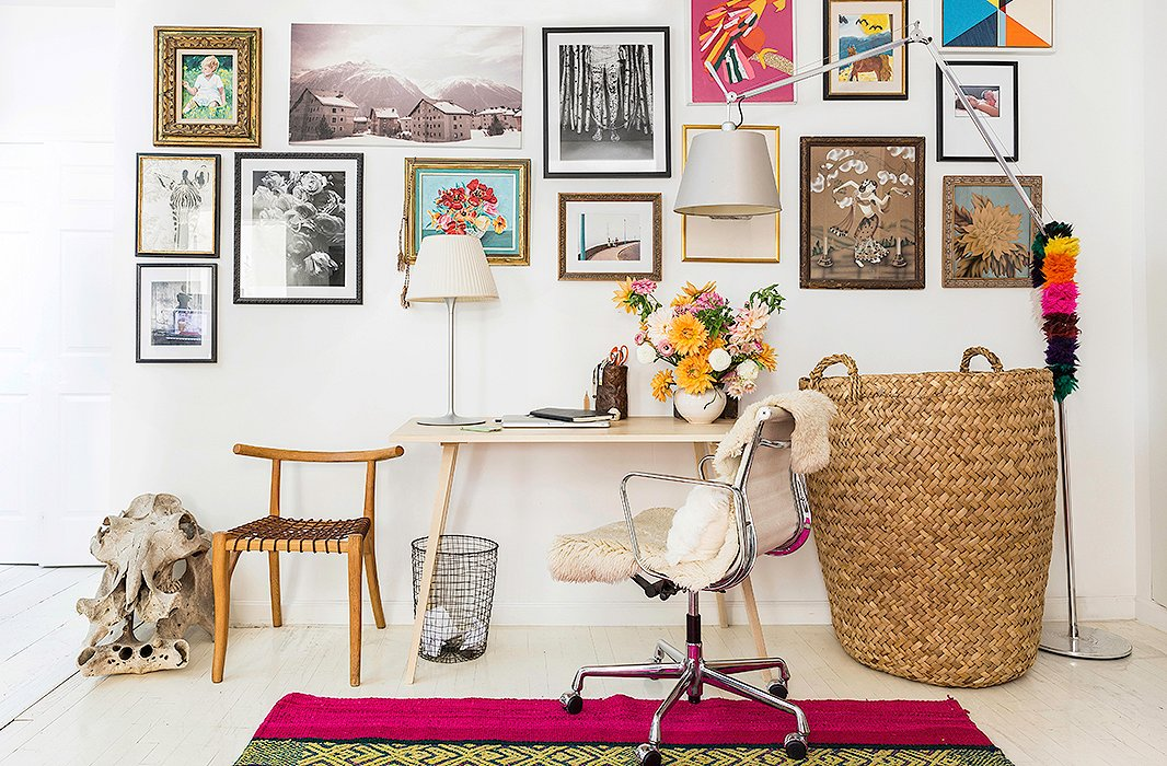"Jenni wanted to keep her home office simple, so she furnished the space with a clean-lined desk and a modern chair. She also installed an inspiration-packed gallery wall filled with photography, paintings, and family snapshots. ""I always like big walls of different art,"" she says. ""Wherever we've lived I always try to do a collage of artwork."""