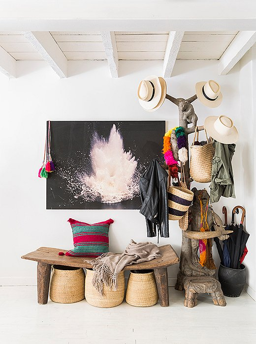 "Hats and bags from Jenni's online textiles shop, Intiearth, hang on a carved coatrack besides a photograph by Hans Gissinger in the entryway. ""We don't wear shoes in the house, so everybody has a basket they put their shoes in."""