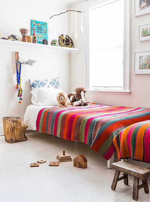 "Twin beds line a wall in Son and Harmony's room. ""That was the best way to fit them in the space,"" she says. ""I'm not into bunk beds, and I feel that it promotes brotherly bonding."" She also installed shelves above each bed for toys and books. ""They do their own curating on their bookshelf."""