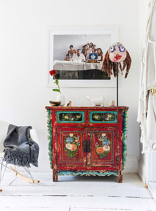 "One of Jenni's favorite pieces in the house is the portrait of family and friends that hangs in a hallway above a vintage Chinese chest. ""It just kind of captured everybody so perfectly,"" she says."