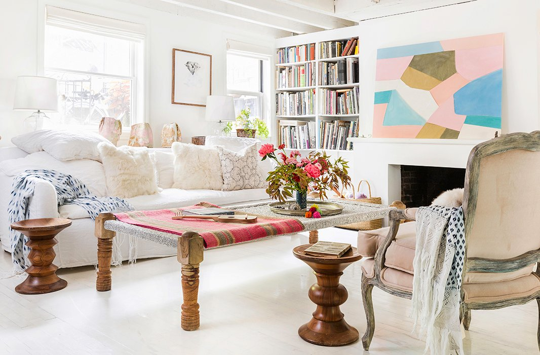 "The living area is awash in light and filled with cozy spots to curl up and relax. ""The sofa is very comfortable,"" Jenni says. ""That was a requirement, actually."" To perk up the white space she used soft pinks, including a painting by her friend Meghan Petras and a frazada, or Peruvian rug, from Intiearth, which she draped over the Indian daybed that serves as a coffee table."