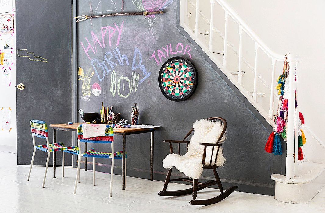 """I always try to have an art station for the kids in the central living area,"" explains Jenni, who set up a spot for painting and drawing complete with a chalkboard wall. ""That is the one kid-friendly aspect that I make sure to integrate in."""