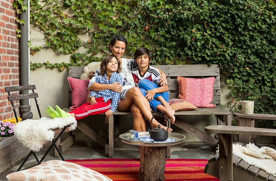 "Jenni relaxes in the backyard with Son, Harmony, and Noa. She likes to pile colorful pillows and sheepskin throws on the cedar bench and the Adirondack chair for comfort and to connect them to the interior space. ""I always outfit the outdoor space to make it feel cozy and inviting,"" she says. ""We do a fire pit in the winter and have string lights for when it gets dark."