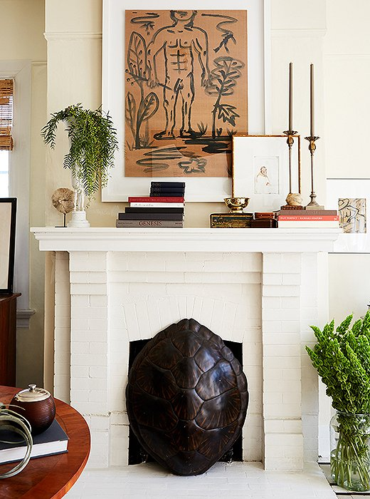 "William used a tortoiseshell to hide the fireplace's unsightly gas heater. The mantel is decorated with candlesticks he bought as a teenager and a brass vase that he updated with a coat of paint. ""It's the power of painting something white,"" he says. ""All of a sudden, it becomes really cool."""