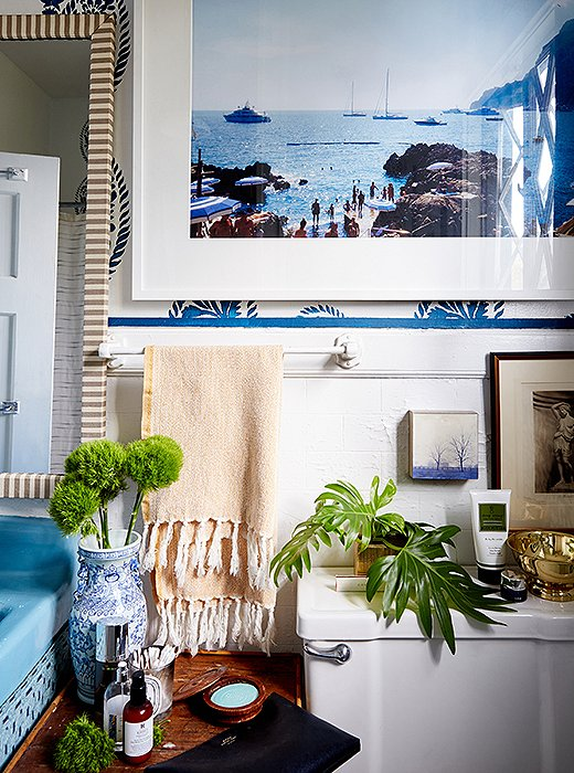 "Instead of installing wallpaper, William used a stencil on the bathroom walls. ""I knew I wanted to incorporate blue in the space, and I'm obsessed with block print,"" he says. He also spray-painted the sink in a coordinating shade and added a skirt to hide storage for towels."