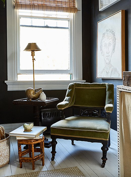 "He arranged a petite seating area in the corner of the bedroom with an antique armchair (""I love all the ornamentation on it"") and a square table he found at an estate sale."