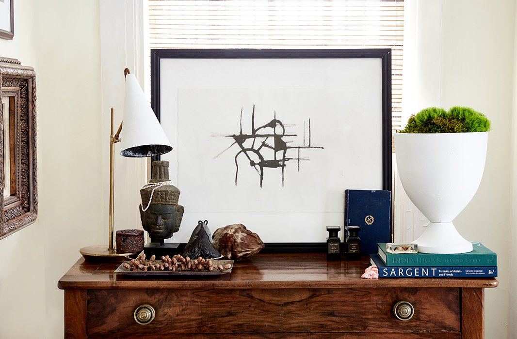 "William paired one of his artworks with a modern lamp and vase for a graphic vignette atop a chest of drawers in the living room. ""I don't use overhead lighting a lot,"" he says. ""I have, like, a million lamps in the house."""